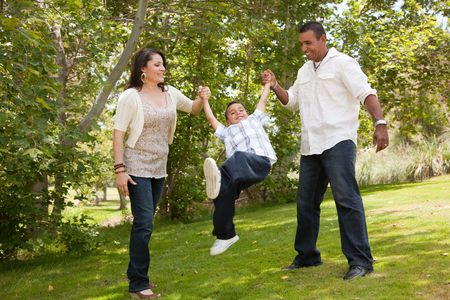 two generation family: Hispanic Man, Woman and Child having fun in the park. Stock Photo