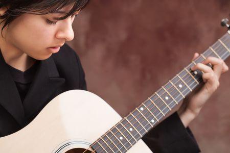 Attractive Ethnic Girl Enjoys Playing Her Guitar. Stok Fotoğraf