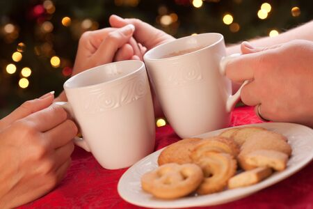 Man and Woman Sharing Hot Chocolate and Cookies in Front of Holiday Lights. Imagens