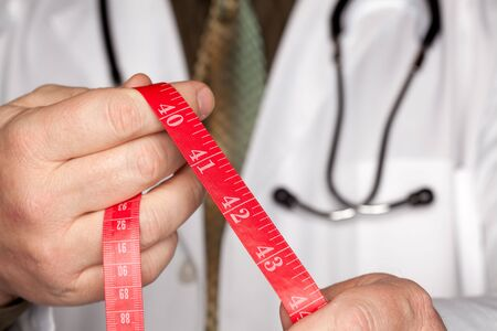 bmi: Doctor with Stethoscope Holding Red Measuring Tape.