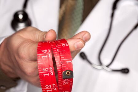 Doctor with Stethoscope Holding Red Measuring Tape. photo