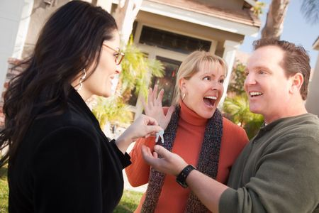 causcasian: Hispanic Female Real Estate Agent Handing Over New House Keys to Excited Couple.