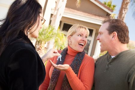 Hispanic Female Real Estate Agent Handing Over New House Keys to Excited Couple. photo