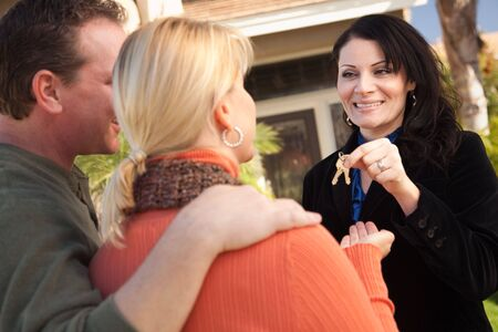 Attractive Hispanic Female Real Estate Agent Handing Over New House Keys to Happy Couple. Archivio Fotografico