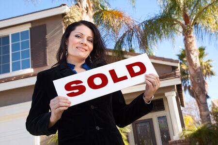 vendiendo: Feliz atractiva mujer de hispanos Holding Sold Sign en frente de la casa.