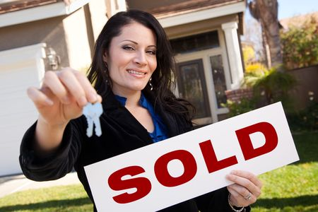 sell: Happy Attractive Hispanic Woman Holding Keys and Sold Sign In Front of House.