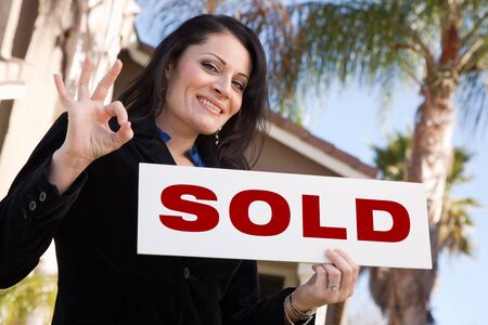 sell: Happy Attractive Hispanic Woman Holding Sold Sign In Front of House.