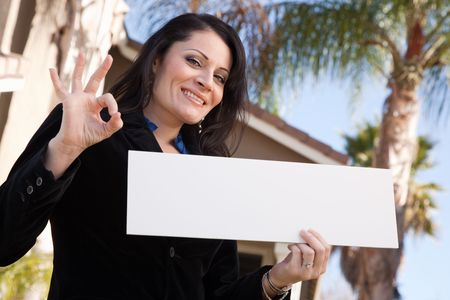 Happy Attractive Hispanic Woman Holding Blank Sign in Front of House. Archivio Fotografico