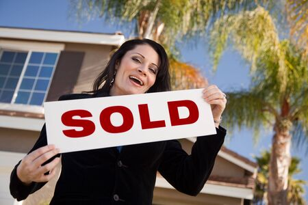 Happy Attractive Hispanic Woman Holding Sold Sign In Front of House.