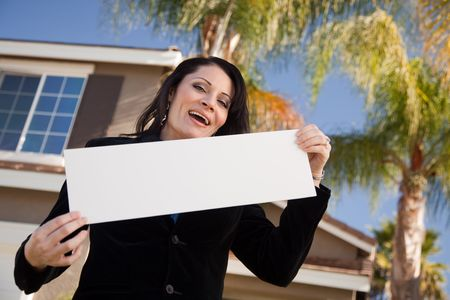 homebuyer: Happy Attractive Hispanic Woman Holding Blank Sign in Front of House. Stock Photo