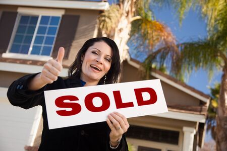 homebuyer: Happy Attractive Hispanic Woman with Thumbs Up Holding Sold Sign In Front of House.