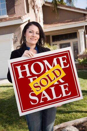 homebuyer: Happy Attractive Hispanic Woman Holding Red Sold Home For Sale Sign In Front of House.