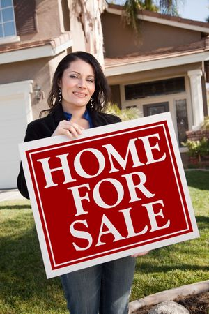 homebuyer: Happy Attractive Hispanic Woman Holding Home For Sale Real Estate Sign In Front of House.