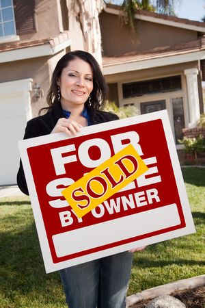 homebuyer: Happy Attractive Hispanic Woman Holding Sold For Sale By Owner Real Estate Sign In Front of House