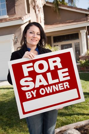 Happy Attractive Hispanic Woman Holding For Sale By Owner Real Estate Sign In Front of House. Фото со стока