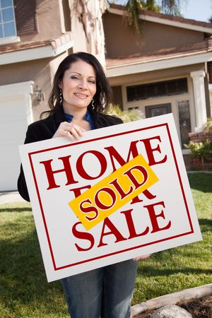 homebuyer: Happy Attractive Hispanic Woman Holding Sold Home For Sale Sign In Front of House.