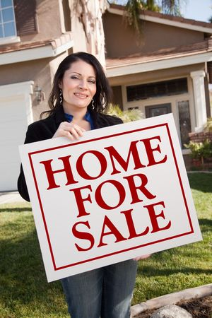 homebuyer: Hispanic Woman Holding Home For Sale Real Estate Sign In Front of House.