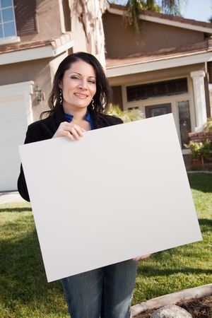 real estate investment: Happy Attractive Hispanic Woman Holding Blank Sign in Front of House. Stock Photo