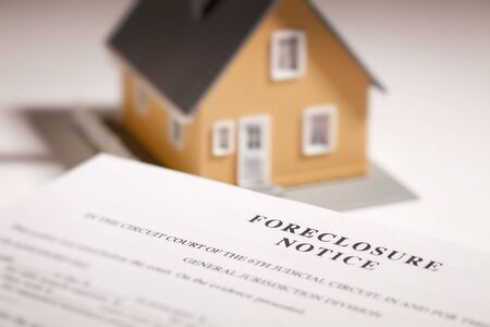 foreclosed: Foreclosure Notice and Model Home on Gradated Background with Selective Focus.