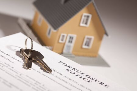 eviction: Foreclosure Notice, House Keys and Model Home on Gradated Background with Selective Focus. Stock Photo