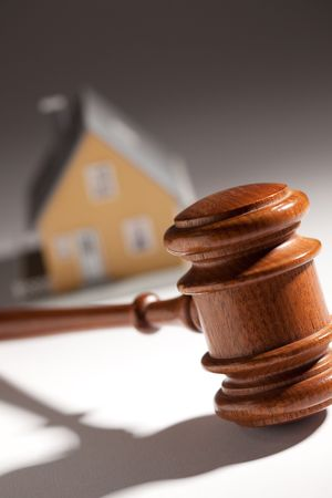 auctions: Gavel and Model Home on Gradated Background with Selective Focus.