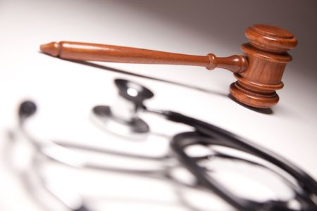 Gavel and Stethoscope on Gradated Background with Selective Focus.
