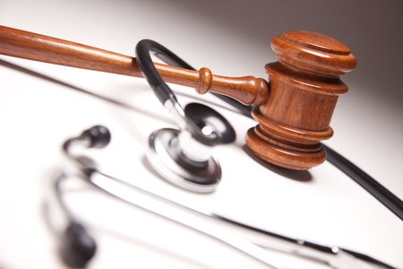 carelessness: Gavel and Stethoscope on Gradated Background with Selective Focus.