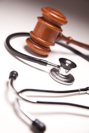 negligence: Gavel and Stethoscope on Gradated Background with Selective Focus.