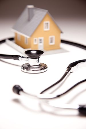 clinician: Stethoscope and Model House on Gradated Background with Selective Focus.