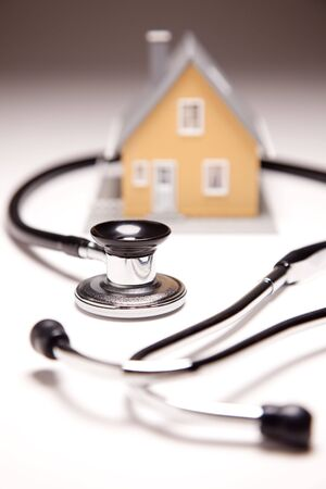 stethoscope: Stethoscope and Model House on Gradated Background with Selective Focus.