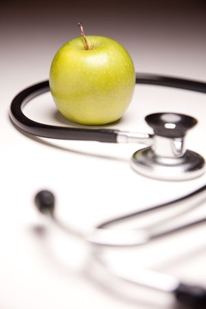 Stethoscope and Green Apple on Gradated Background with Selective Focus. Stock Photo - 6310963