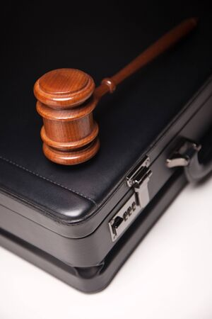 law business: Gavel and Black Briefcase on Gradated Background with Selective Focus - Business Law Concept.