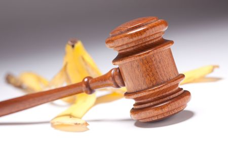 lawsuite: Gavel and Banana Peel on Gradated Background with Selective Focus - Lawsuit Concept.