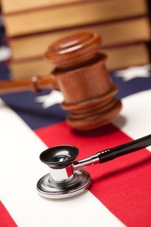 delito: Martillo, Stethoscope y libros sobre la bandera estadounidense con enfoque selectivo.  Foto de archivo
