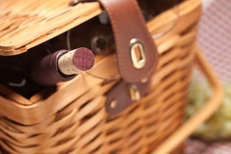 Picknickmand, fles wijn en lege bril op een pastel deken.