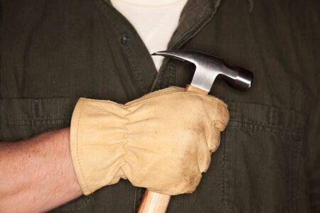 Caucasian Man with Leather Construction Glove Holding Hammer. photo