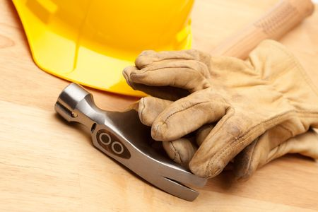 Yellow Hard Hat, Gloves and Hammer on Wood Surface.