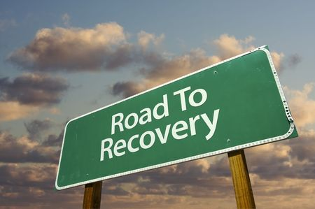 Road To Recovery Green Road Sign with dramatic clouds and sky. Stock Photo