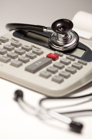 Black Stethoscope on a Calculator with Selective Focus. Stock Photo
