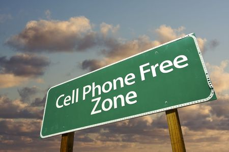 phone: Cell Phone Free Zone Green Road Sign In Front of Dramatic Clouds and Sky.