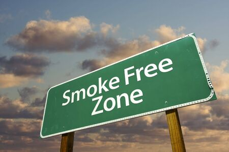 Smoke Free Zone Green Road Sign In Front of Dramatic Clouds and Sky. photo