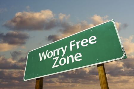 at ease: Worry Free Zone Green Road Sign In Front of Dramatic Clouds and Sky. Stock Photo
