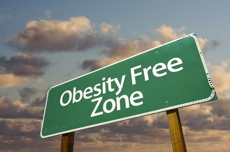 lose weight: Obesity Free Zone Green Road Sign In Front of Dramatic Clouds and Sky.