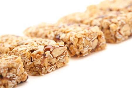 roughage: Row of Several Granola Bars Isolated on a White Background with Narrow Depth of Field. Stock Photo