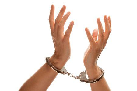 handcuffed: Geboeid vrouw wanhopig verhogen handen in de lucht geïsoleerd op een witte achtergrond. Stockfoto