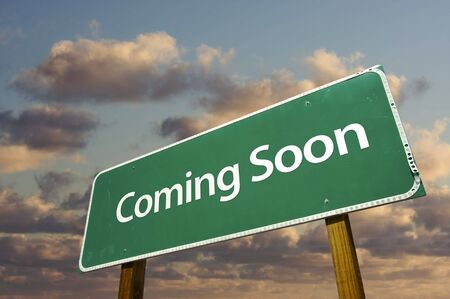 Coming Soon Green Road Sign Over Dramatic Clouds and Sky. photo