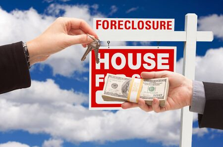 repossessing: Handing Over Cash For House Keys in Front of Foreclosure Sign and Cloudy Blue Sky. Stock Photo