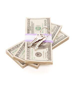 repossessing: House Keys on Stack of Money Isolated on a White Background - Cash for Keys Program. Stock Photo