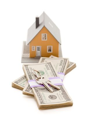 repossessing: Home and House Keys on Stack of Money Isolated on a White Background - Cash for Keys Program.