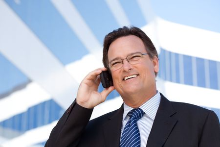 Confident, Handsome Businessman Smiles as He Talks on His Cell Phone.